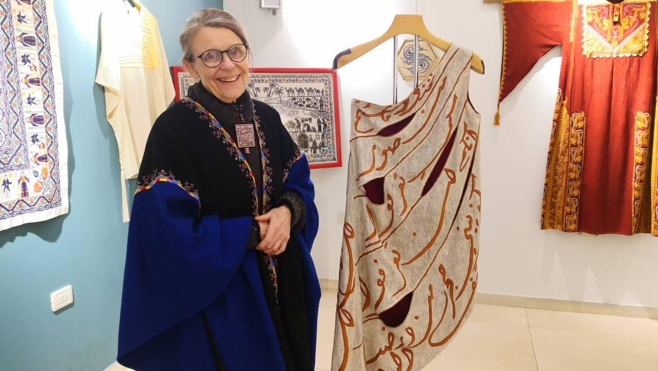 هايكة فيبر أمام فستان من تصميمها وقد طُرزت عليه كلمات قصيدة لمحمود درويش
